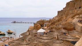 Praia rochosa com os guarda-chuvas perto do penhasco no Mar Vermelho no recife de corais Egypt video estoque