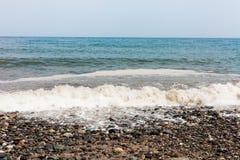 Praia rochosa com pedras coloridas Céu azul sem nuvens Dia nebuloso no lado da praia com as ondas que batem o litoral Espuma do m foto de stock royalty free