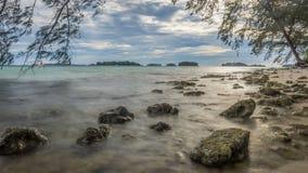 A praia rochosa com um céu azul nebuloso dramático fotos de stock