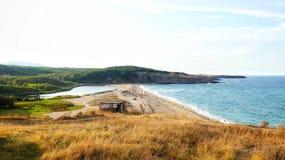 Praia rochosa da costa com farol imagem de stock