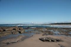 Praia rochosa do oceano com areia e ondas que rolam dentro no fundo Fotos de Stock Royalty Free