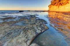 Praia rochosa durante o nascer do sol Imagem de Stock Royalty Free