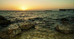 Praia rochosa no crepúsculo Imagens de Stock