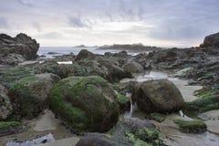 Praia rochosa no por do sol Imagens de Stock Royalty Free