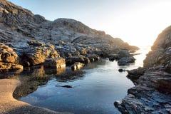 Praia rochosa pequena na luz do por do sol fotos de stock royalty free