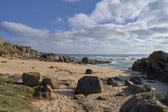 Praia rochosa sob com nuvens fotografia de stock
