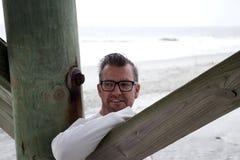 Praia South Carolina do insensatez, o 17 de fevereiro de 2018 - homem branco ao lado da pilha de madeira com o braço que pendura  foto de stock royalty free
