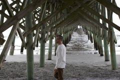 Praia South Carolina do insensatez, o 17 de fevereiro de 2018 - homem branco que anda sob o cais da praia Fotografia de Stock