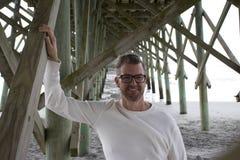 Praia South Carolina do insensatez, o 17 de fevereiro de 2018 - homem em camisa branca longsleeved que está sob o cais da praia fotos de stock