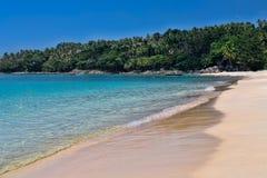 Praia tropical com água dos azuis celestes fotografia de stock