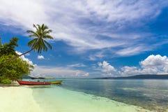 Praia tropical com barcos locais, palma de coco, a areia branca e a água de turquesa fotografia de stock royalty free