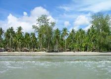 Praia tropical com bungalows e palmeiras Fotos de Stock Royalty Free
