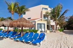 Praia tropical com deckchairs azuis Fotografia de Stock Royalty Free