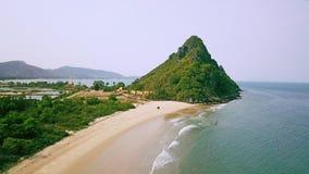 Praia tropical com oceano azul e o penhasco verde da floresta úmida Vídeo aéreo filme