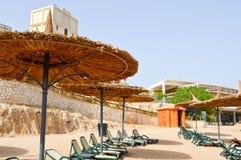 Praia tropical de Sandy em férias, um recurso tropical com camas do sol, vadios do sol e guarda-sóis sob a forma dos chapéus de p fotografia de stock