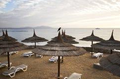 Praia vazia com guarda-chuvas da palha Foto de Stock Royalty Free