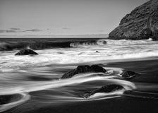 Praia vulcânica preta com pedras, movimento da água na exposição longa imagens de stock royalty free