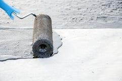Praimer de bitume de peinture de travailleur de Roofer sur la surface en béton par t Photo stock
