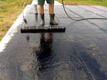 Praimer del bitume della pittura del lavoratore del Roofer a superficie di calcestruzzo dall'impermeabilizzazione della spazzola  fotografia stock libera da diritti