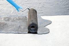 Praimer do betume da pintura do trabalhador do Roofer na superfície concreta por t Foto de Stock Royalty Free