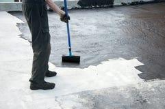 Praimer do betume da pintura do trabalhador do Roofer na superfície concreta por t fotografia de stock