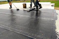 Praimer för bitumen för Rooferarbetarmålning på konkret yttersida vid waterproofingen för rullborste royaltyfri bild