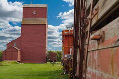 Prairie Farm Life. A train travelling on the tracks by a prairie grain elevator Royalty Free Stock Photo