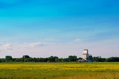Prairie Field. A prairie field with a grain elevator in the distance shot with lots of copyspace in the sky Stock Photos