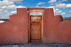 Prairie Gate. Adobe wall with a kiva step design and carved wooden gate in front of a New Mexico prairie royalty free stock images