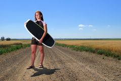 Prairie Girl Wake Boarder. A pretty young woman on dirt road with wake board, looking off into the prairie, no sign of water any where Stock Images
