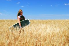 Prairie Girl in Wheat Field. A pretty teenage girl with wakeboard in durham wheat field royalty free stock photography