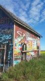 Prairie grafitti. A grafitti covered shed in a field Stock Images