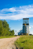 Prairie Grain Elevator. A prairie grain elevator with a dirt road running to it shot on a partly cloudy day Stock Photography