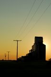 Prairie Grain Elevator Sunset. A prairie elevator silhouette against a sunset Royalty Free Stock Photography