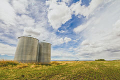 Prairie Landscape with Grain Silos. Metal grain silos on a prairie landscape with a blue cloudy sky stock photography