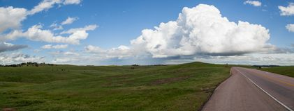Prairie Panoramic with Road. A panoramic view of a spring green prairie next to the road through Wind Cave National Park with ominous storm clouds in the distant stock photos