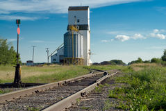 Prairie Railroad Tracks. Running along beside a tall grain elevator and vanishing in the distance Royalty Free Stock Image