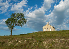 Prairie Schoolhouse. Nineteenth century schoolhouse in the Kansas Flint Hills with a single tree and blue sky background with clouds Stock Photos