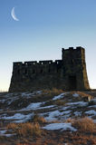 Prairie winter. A castle standing on snow-covered prairie under a moonlit evening Stock Image