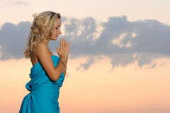 Praise. Young blond girl praying outdoors at evening time stock photo