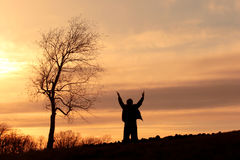 Praise. Silhouette of a man on a hill standing by a tree with his arms lifted in the air stock image