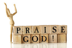 Praise God!. Rustic alphabet blocks arranged to say Praise God!    A wooden artist's manniquin stands nearby with face and hands upraised to heaven.  Isolated Stock Images
