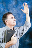 Praise God!. A man in a posture of praise and worship with an old bible held tightly to his chest Royalty Free Stock Image