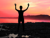 Praise the lord. A woman silhouette with his arms raised in worship royalty free stock images