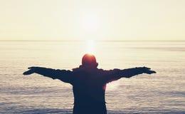 Praise rejoice person hope silhouette celebrating against sea ocean water arms up beating Coronavirus