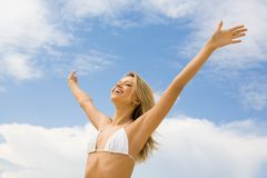 Praise to God. Portrait of happy girl in white bikini praising God with her eyes shut and raised arms on background of cloudy sky Stock Images