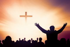 Praise and worship concept:Silhouette of Christian prayers raising hand while praying to the Jesus royalty free stock photo