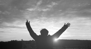 Praise and worship concept: Silhouette human raising hands to praying God on blurred cross with crown of throne sunset background royalty free stock image