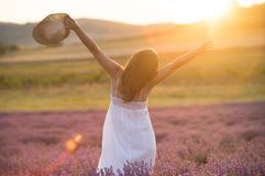 Praising the beauty of life. Beautiful young woman with a white dress and a straw hat standing in the middle of a lavender field at in the golden light of the Stock Photos