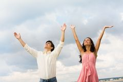 Praising couple. Portrait of happy couple standing with raised arms on background of cloudy sky stock photography